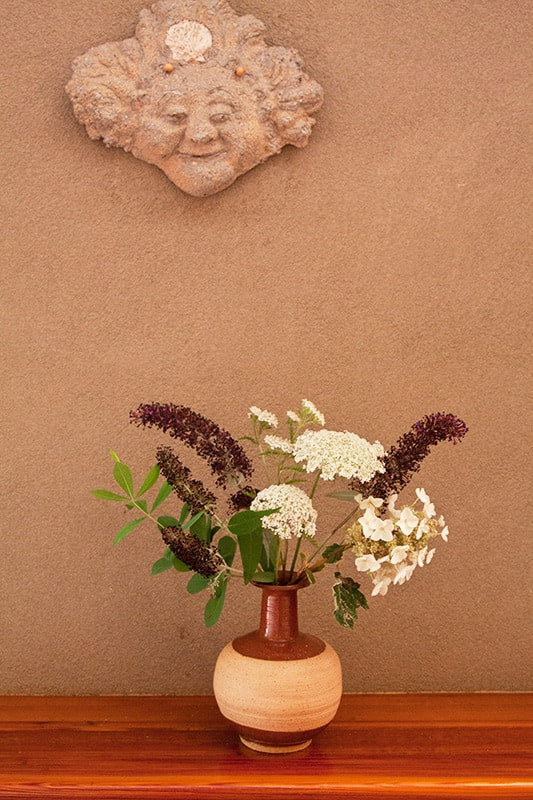 Whimsical ceramic face on wall with a flower filled vase below