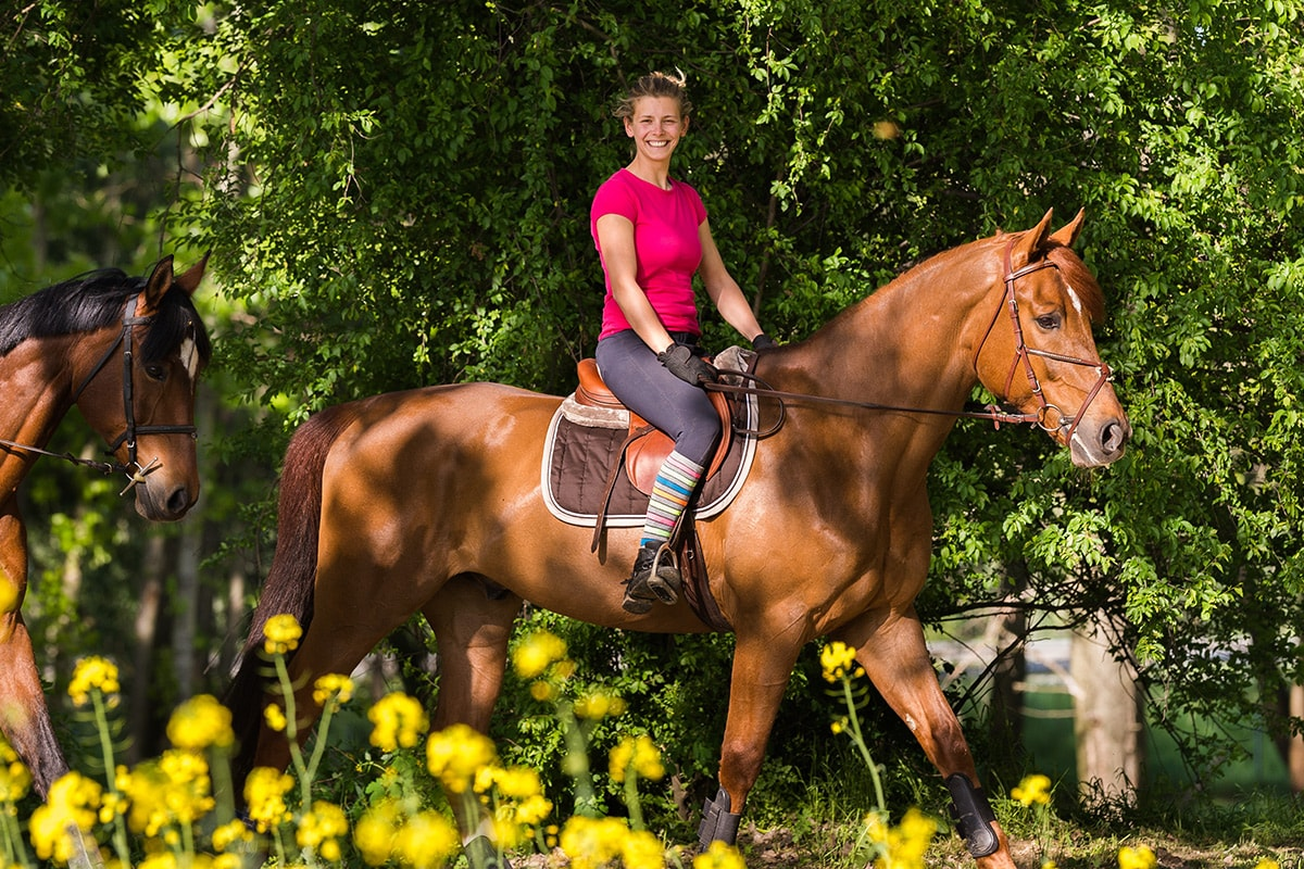 Woman riding horseback through a meadow