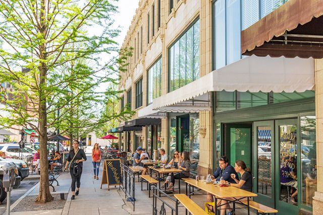 People relax and eat outside in downtown Asheville at the Grove Arcade