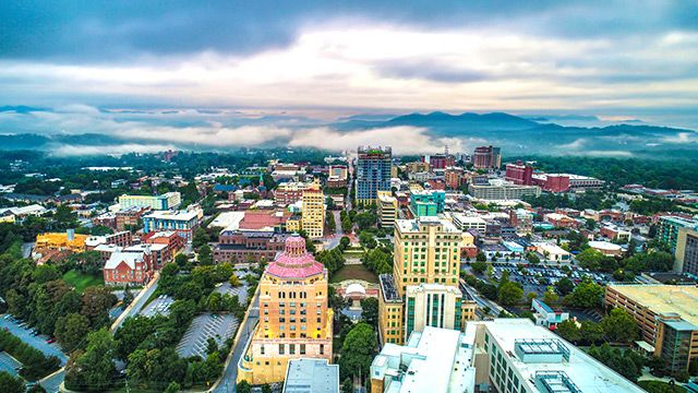 Downtown Asheville as seen from above, with the misty Blue Ridge Mountains