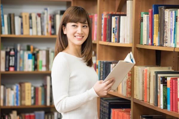 図書館で本棚の前に立って本を読む女子大生1@AC