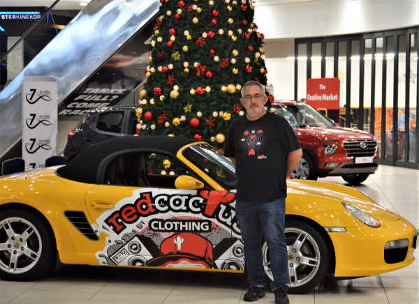Louis Weber from Red Cactus Clothing stands next to the 2007 Porsche Boxter 987 that's up for grabs.