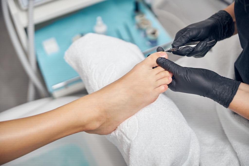 Professional in sterile gloves doing manicure for woman
