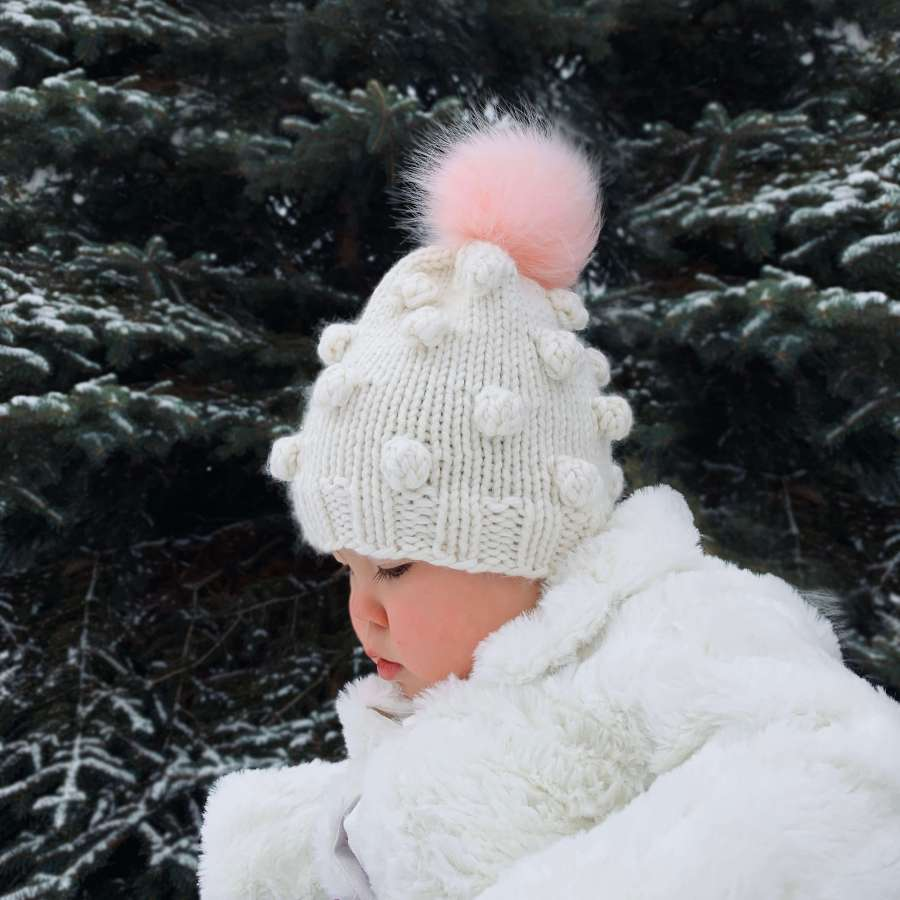 toddler wearing bobble hat.