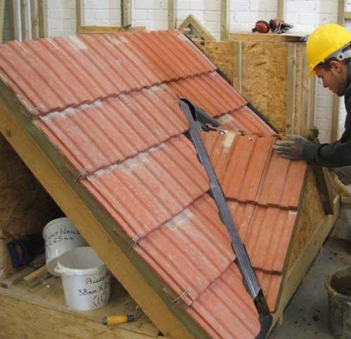 Diploma candidate preparing to add ridge to roof rig, also shows work to verge and valley