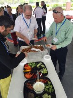 The group is treated to a gator meat appetizer before lunch. HM Clause Seed Co CEO Matthew Johnston (right) takes his turn.