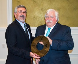 Rick Byler, right, received the traditional gin saw from incoming NCGA President Ron Craft, on being named the NCGA's 2016-17 Charles C. Owen Distinguished Service Award recipient.