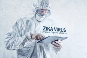 Zika virus concept, medical worker in protective clothes using digital tablet computer to access internet and study symptoms, diagnosis and treatment of this illness.