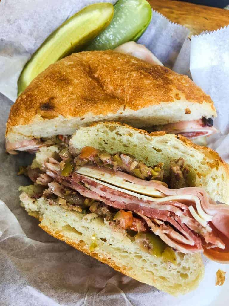 A muffaletta with meats and olive spread in a basket and a pickle from Stein's Deli in New Orleans.