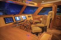 The enclosed flybridge is well equipped with centerline controls, a large settee and custom table, and dayhead for convenience. Photo: JLambertPhotos.com