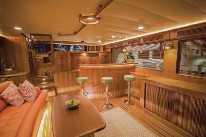 Twin doors open from the aft deck to the salon and rich furnishings: a pair of lounge chairs (not shown), large sofa, custom wooden table, writing desk, storage, and large-screen TV. Photo: JLambertPhotos.com
