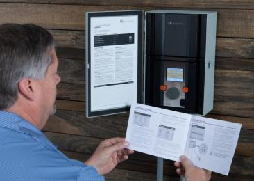 man reading instructions next to electrical box