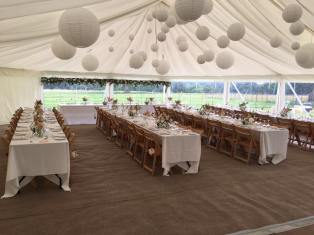 Trestle tables and lots of paper lanterns adorned this wedding marquee at Hill Place in Swanmore.