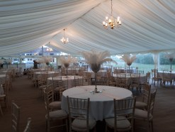Fabulous white feathers and jewelled vases make a dramatic display in this large wedding marquee.