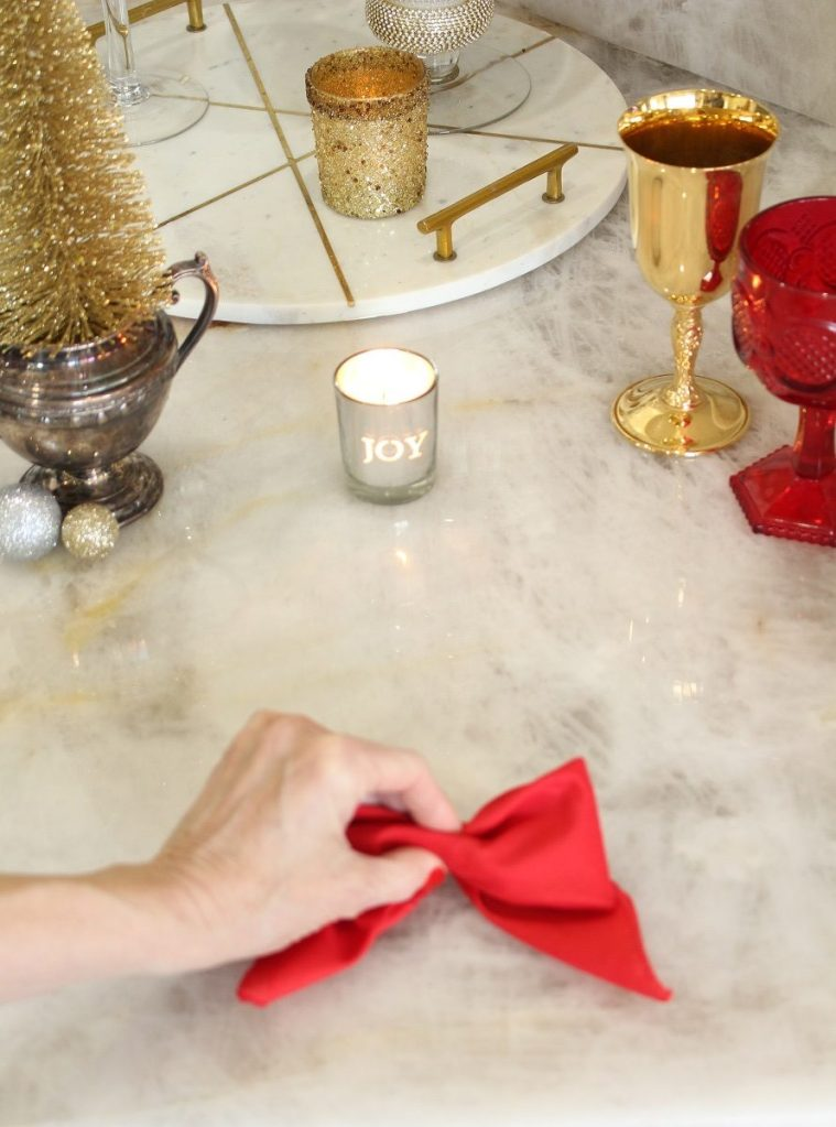 Hand holding Red Napkin folded as a Bow