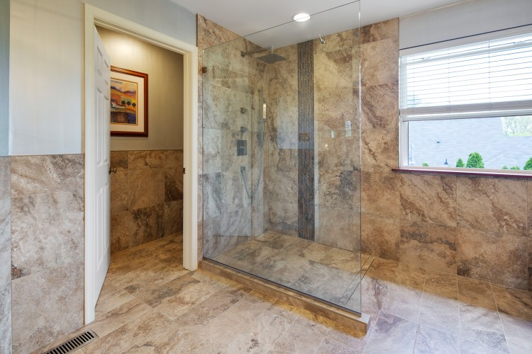 The over-sized shower stall with seamless glass surround and private loo.
