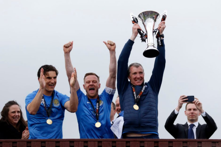Jim Gannon lifts the trophy for Stockport
