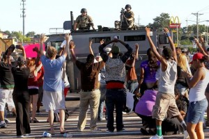 Residents of Ferguson, MO protest while St. Louis County Police look on. Photo Credit: Wiki Photos