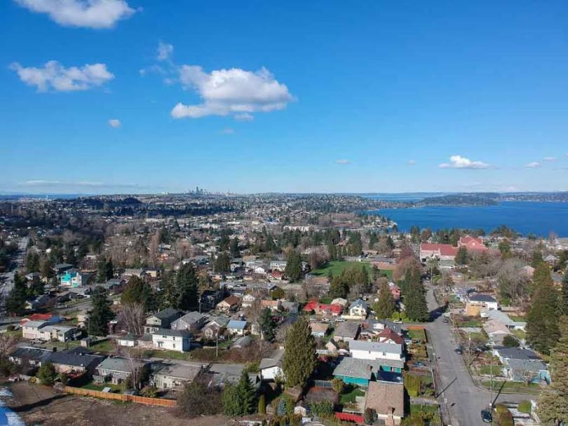 Aerial image of the Rainier Beach neighborhood--houses in the foreground; south-western Lake Washington and a tiny Seattle city skyline in the background