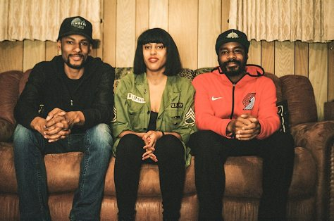 Three gorgeous young, hip black people sit on a brown couch, hands together, smiling, a faux-wood paneled wall with old-ass looking curtains behind them. This could be your grandparents' house.