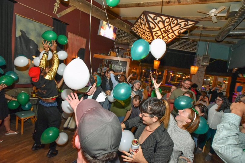 a crowd of people in a classy bar catch and play with white and green balloons as they fall from the ceiling.