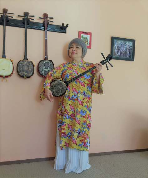 A woman with grey hair styled in a bob wears a long, yellow and white layered robe with a pattern that might be sea creatures in red, pink, orange, and blue stands holding a sanshin (a three-stringed Okinawan musical instrument). Three more sanshins hang on a pale peach wall next to and behind her.