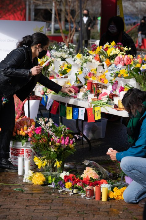 Community members light candles and leave flowers on a large outdoor shrine in Seattle's Hing Hay park. (Photo: Chloe Collyer)