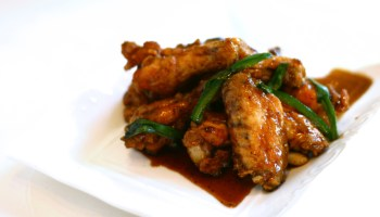 A savory dish of glazed chicken wings with green peppers sits on a white square plate