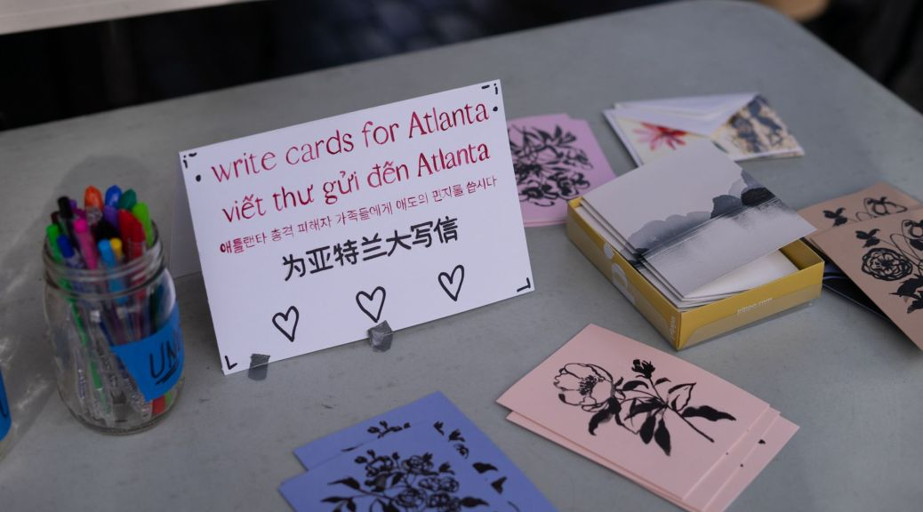 "White card that reads ""write cards for Atlanta"" in English, Vietnamese, Korean, and Chinese sits on table with stationery and pens"