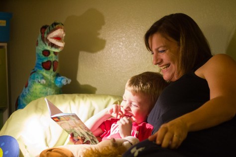 Female-presenting individual reads to a male-presenting child in bed with stuffed dinosaur in the background