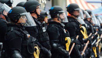 Riot police officers lined up with yellow wrist ties and batons