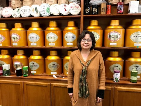 Female-presenting individual stands in front of shelves filled with gold cannisters of tea
