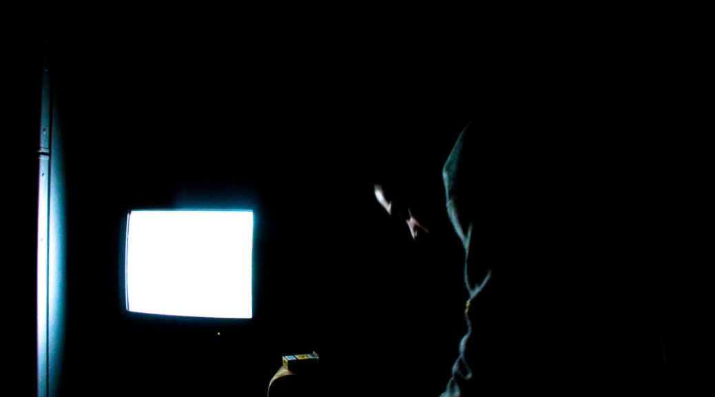 Male-presenting person hunched over in darkened room in front of white TV screens