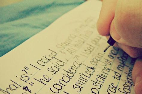 Hand writing text across a notebook