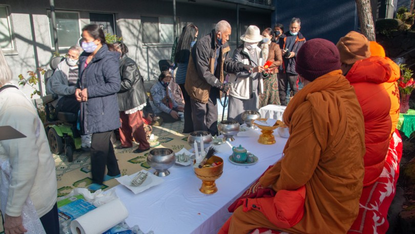 Residents of Mt. Baker Village participate in a ceremony to give offerings to the Buddhist Monks of Watt Dhammackakaram.