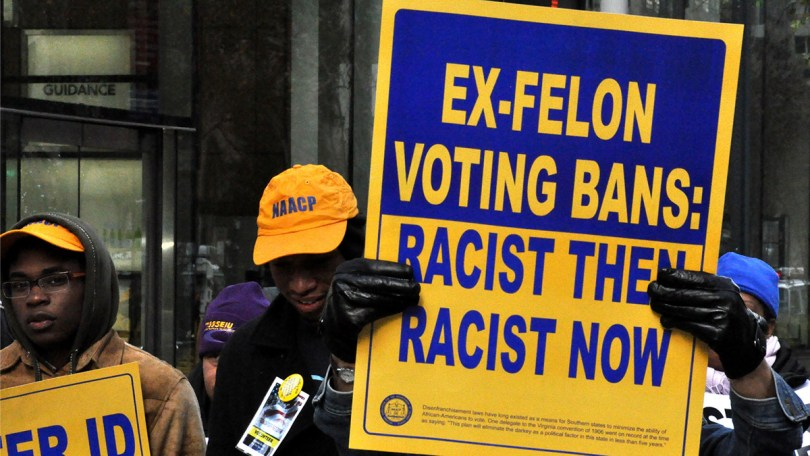"""Protestors hold blue and yellow signs that read """"EX-FELON VOTING BANS: RACIST THEN, RACIST NOW"""""""