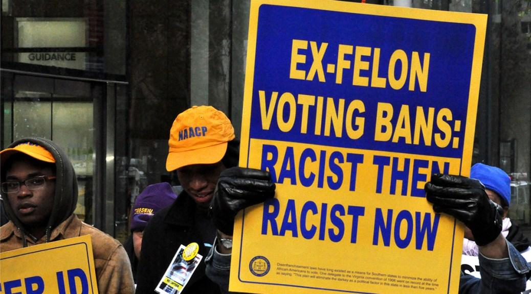 "Protestors hold blue and yellow signs that read ""EX-FELON VOTING BANS: RACIST THEN, RACIST NOW"""