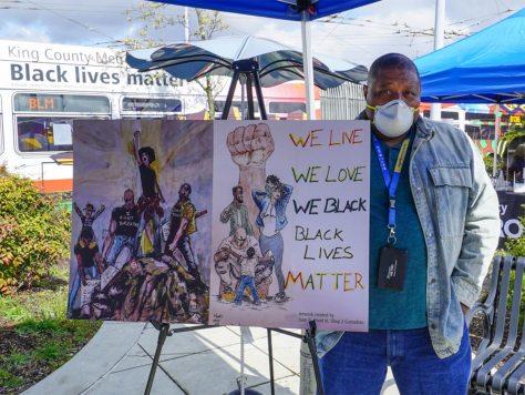 Metro employee Juan G. Hood standing with his BLM-inspired artwork