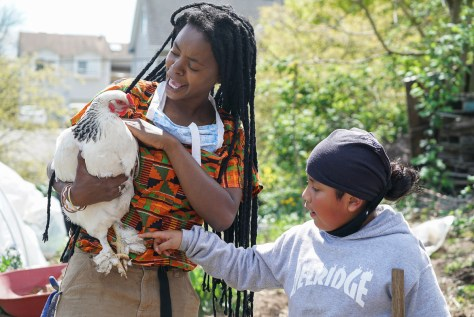 Nyema Clark, founder and director of Nurturing Roots Farm, holds a white chicken while a youth reaches out to pet the chicken's feet.