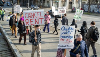 "Protestors march outside Seattle City Hall carrying signs that read ""Cancel Rent,"" ""Quality Public Housing for All,"" and ""Tax the Rich."""