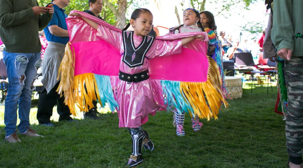 Youth dances in pink Indigenous regalia with yellow, blue, and pink adornments