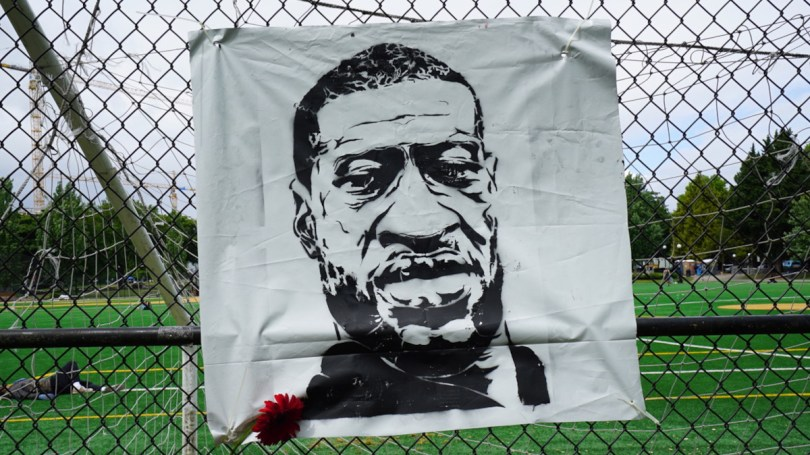 Memorial on a fence depicting George Floyd on Capitol Hill during last summer's Black Lives Matter protests.
