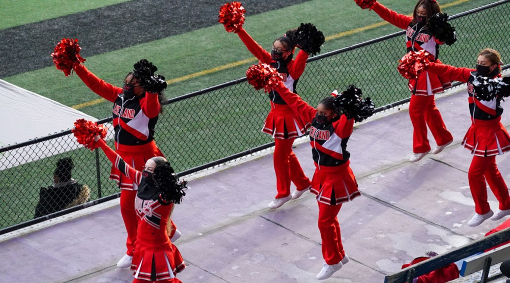 Cleveland High School cheerleaders cheer with facemasks at a high school football game.