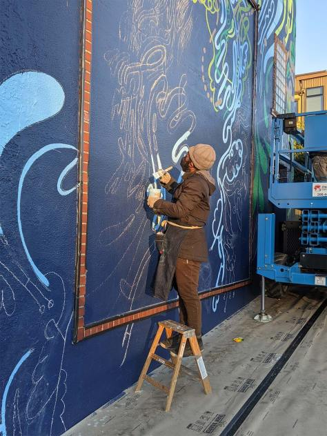 """Moses Sun paints his mural """"Flourish Together"""" on the exterior of the Columbia City Theater"""