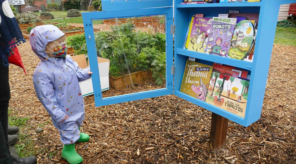 Child in purple and green rain gear visits a blue Page Ahead Book Oasis stocked with children's books.