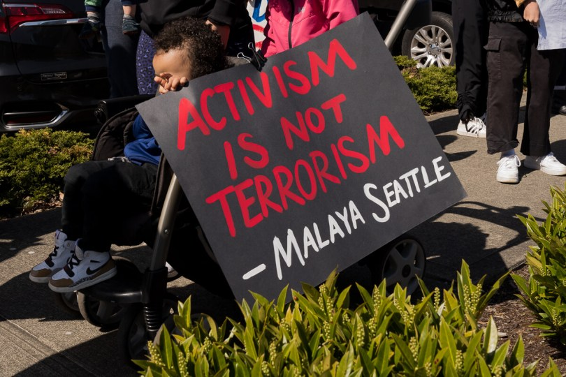 """A young child holds a sign during the rally that reads """"Activism is not Terrorism - Malaya Seattle"""""""