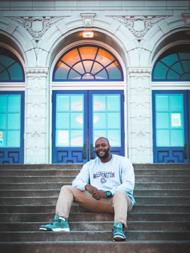 Photo of Anthony Washington sitting on the steps of a school.