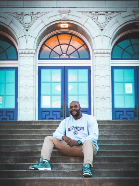 Photo of Anthony Washington sitting on the steps of a school.