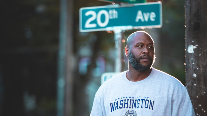 """Photo of Anthony Washington standing in front of a street sign that reads """"20th Avenue"""""""