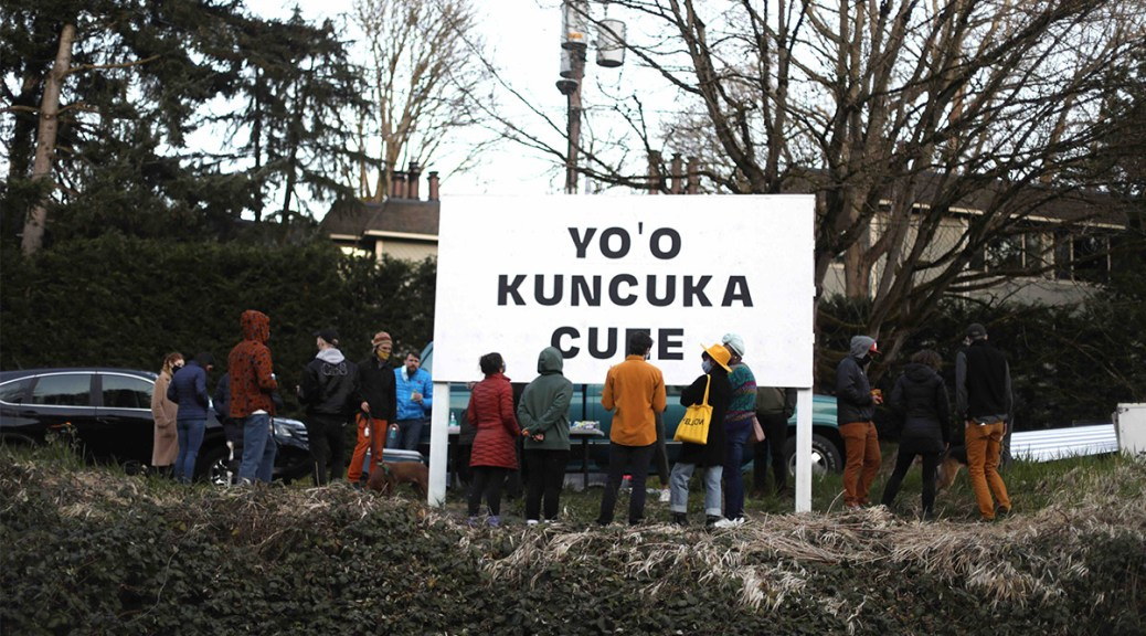 "Photo of people gathered around a white textboard with black text that reads ""YO'O KUNCUKA CU[obscured letter]E"""
